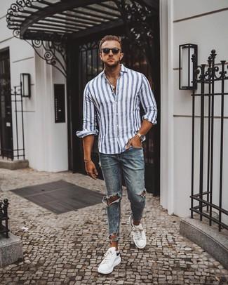 Comment porter: chemise à manches longues à rayures verticales blanc et bleu, jean skinny déchiré bleu, baskets basses en cuir blanches et noires, lunettes de soleil noires