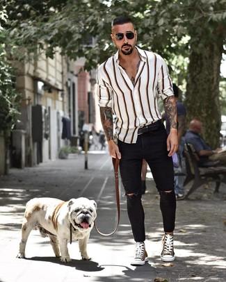 Comment porter: chemise à manches longues à rayures verticales blanche, jean skinny déchiré noir, baskets montantes en toile olive, ceinture en cuir noire