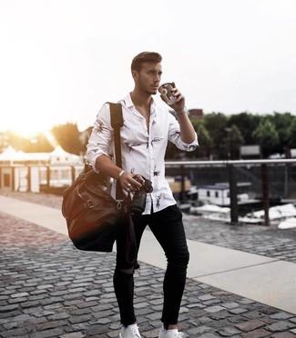 Comment porter: chemise à manches longues imprimée blanche et noire, jean skinny déchiré noir, chaussures derby en cuir blanches, fourre-tout en cuir marron foncé