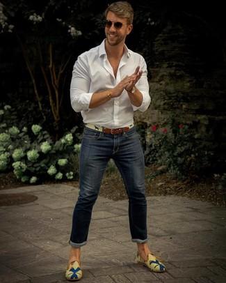 Comment porter: chemise à manches longues blanche, jean skinny bleu marine, slippers en toile imprimés multicolores, ceinture en toile beige