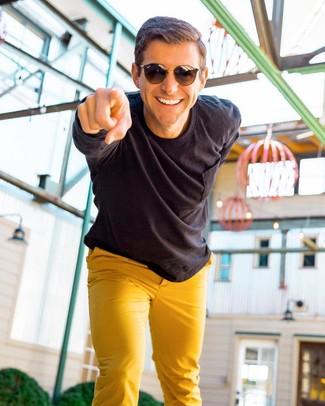 Comment porter: chemise à manches longues noire, pantalon chino moutarde, lunettes de soleil marron foncé