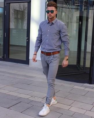 Comment porter: chemise à manches longues en chambray grise, pantalon chino gris, baskets basses en cuir blanches, ceinture en cuir tabac