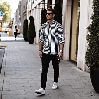 Comment porter: chemise à manches longues à rayures verticales blanche et noire, pantalon chino noir, baskets basses en cuir blanches, lunettes de soleil noires