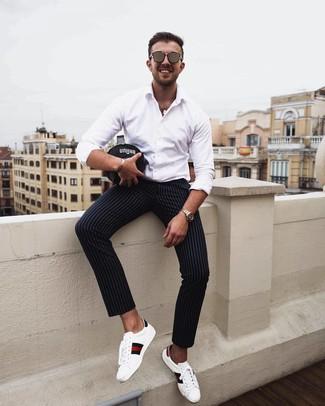 Comment porter: chemise à manches longues blanche, pantalon chino à rayures verticales noir, baskets basses en cuir imprimées blanches, lunettes de soleil marron