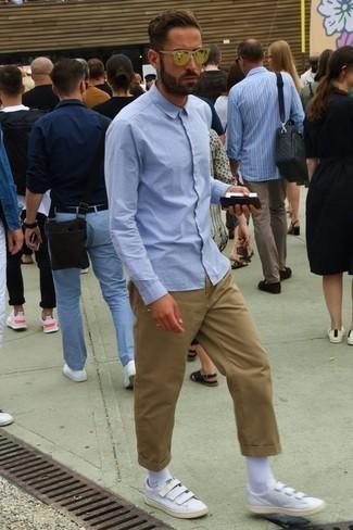 Comment porter un pantalon chino marron clair: Pense à associer une chemise à manches longues bleu clair avec un pantalon chino marron clair pour un déjeuner le dimanche entre amis. Pour les chaussures, fais un choix décontracté avec une paire de des baskets basses en cuir blanches.