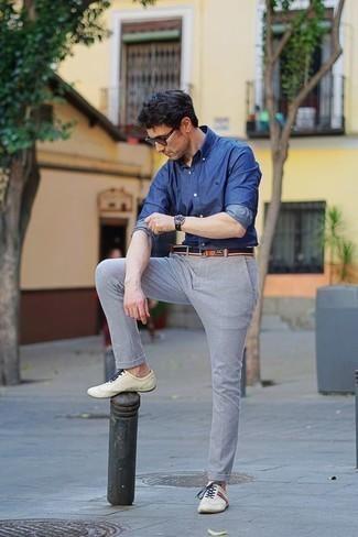 Comment porter une chemise à manches longues en chambray bleue: Essaie d'associer une chemise à manches longues en chambray bleue avec un pantalon chino gris pour obtenir un look relax mais stylé. Une paire de des baskets basses en cuir beiges apporte une touche de décontraction à l'ensemble.