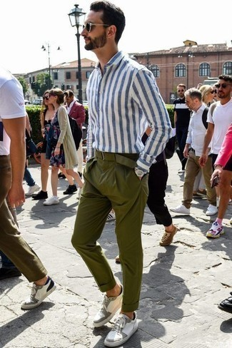 Comment porter un pantalon chino olive: Pense à associer une chemise à manches longues à rayures verticales blanc et bleu avec un pantalon chino olive pour une tenue confortable aussi composée avec goût. Une paire de des baskets basses en cuir blanches est une option judicieux pour complèter cette tenue.