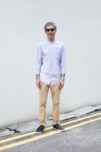 Comment s'habiller après 40 ans: Opte pour une chemise à manches longues bleu clair avec un pantalon chino marron clair pour une tenue idéale le week-end. Si tu veux éviter un look trop formel, assortis cette tenue avec une paire de des baskets basses en toile noires.