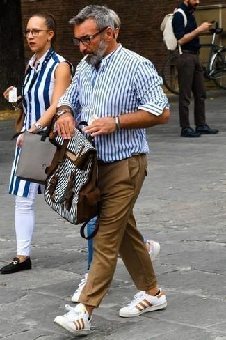 Comment porter un pantalon chino marron clair: Essaie d'associer une chemise à manches longues à rayures verticales blanc et bleu avec un pantalon chino marron clair pour obtenir un look relax mais stylé. Complète ce look avec une paire de des baskets basses en cuir imprimées blanches.