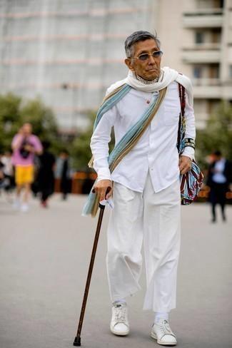 Comment s'habiller après 60 ans: Associer une chemise à manches longues blanche avec un pantalon chino blanc est une option confortable pour faire des courses en ville. Une paire de baskets basses en cuir blanches apportera un joli contraste avec le reste du look.