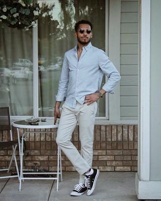 Tendances mode hommes: Harmonise une chemise à manches longues bleu clair avec un pantalon chino gris pour obtenir un look relax mais stylé. Mélange les styles en portant une paire de baskets basses en toile noires et blanches.