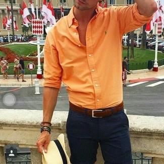 Comment porter: chemise à manches longues orange, pantalon chino noir, chapeau de paille beige, ceinture en cuir marron foncé