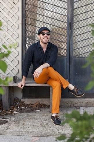 Comment porter: chemise à manches longues noire, pantalon chino orange, chaussures bateau en cuir noires, casquette plate noire