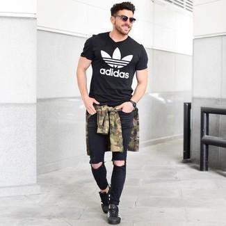 Comment porter: chemise à manches longues camouflage olive, t-shirt à col rond imprimé noir et blanc, jean skinny déchiré noir, baskets basses en cuir noires