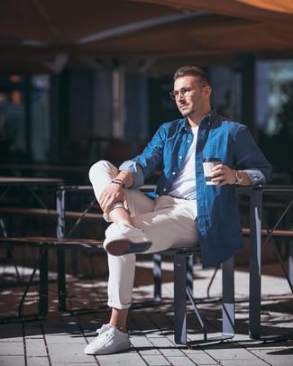 Comment porter: chemise à manches longues en chambray bleue, t-shirt à col rond blanc, pantalon chino beige, baskets basses en cuir blanches