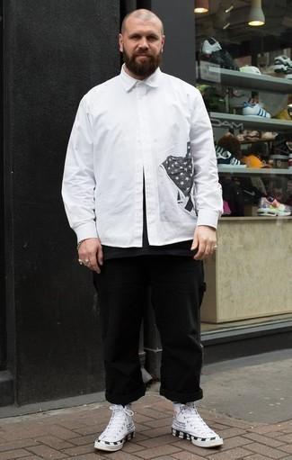 Comment porter un t-shirt à col rond noir: Harmonise un t-shirt à col rond noir avec un pantalon chino noir pour affronter sans effort les défis que la journée te réserve. Jouez la carte décontractée pour les chaussures et choisis une paire de baskets montantes en toile imprimées blanches et noires.