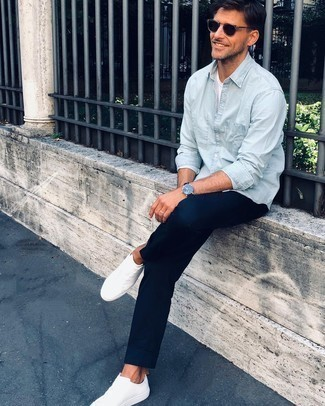 Comment porter des baskets basses en toile blanches: Choisis une chemise à manches longues en chambray bleu clair et un pantalon chino bleu marine pour un look de tous les jours facile à porter. Tu veux y aller doucement avec les chaussures? Termine ce look avec une paire de baskets basses en toile blanches pour la journée.