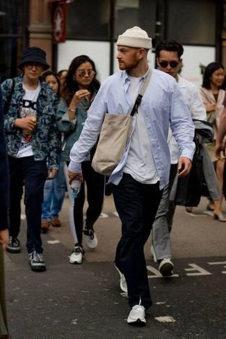 Comment s'habiller au printemps: Opte pour une chemise à manches longues bleu clair avec un pantalon chino noir pour une tenue idéale le week-end. Mélange les styles en portant une paire de chaussures de sport blanches. Nous adorons ce look, très printanière.