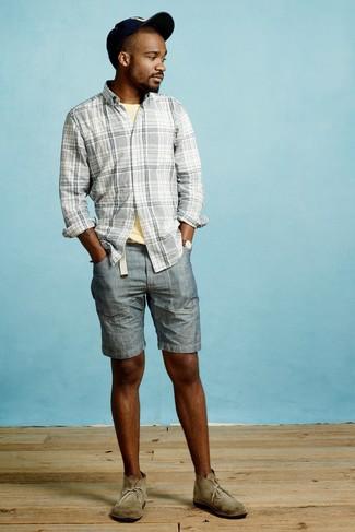 Comment porter: chemise à manches longues écossaise grise, t-shirt à col rond jaune, short en denim bleu, bottines chukka en daim olive