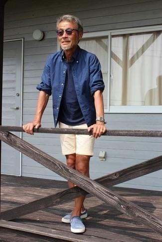 Tendances mode hommes: Associe une chemise à manches longues en chambray bleue avec un short en lin beige pour un déjeuner le dimanche entre amis. Cette tenue est parfait avec une paire de des baskets à enfiler bleu clair.