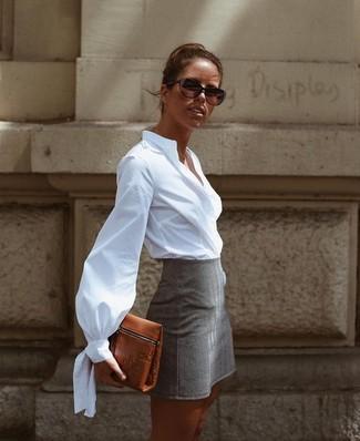 Porte une chemise de ville blanche et une minijupe grise pour achever un look chic.