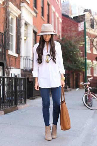 Comment porter: chemise de ville blanche, jean skinny bleu, bottines en daim beiges, sac fourre-tout en cuir tabac
