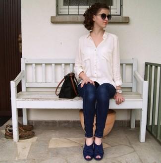 Comment porter: chemise de ville blanche, jean skinny bleu marine, escarpins en daim bleu marine, sac fourre-tout en cuir noir