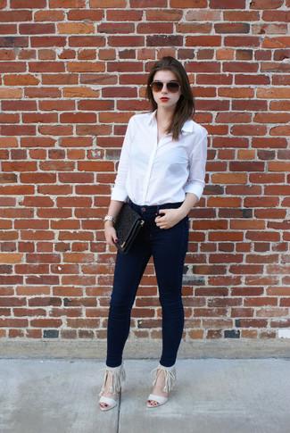 Comment porter: chemise de ville blanche, jean skinny bleu marine, sandales à talons en daim à franges beiges, pochette en cuir découpée noire