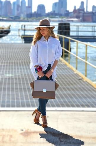 Comment porter: chemise de ville à rayures verticales bleue, jean skinny bleu marine, sandales à talons en daim marron, cartable en cuir marron