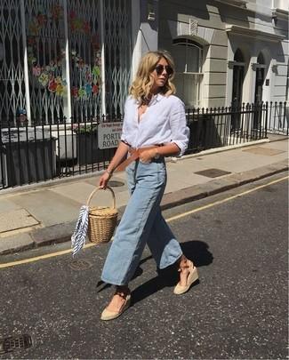Comment porter: chemise de ville en lin blanche, jupe-culotte en denim bleu clair, sandales compensées en toile beiges, pochette de paille marron clair
