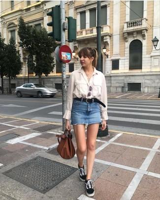 Comment porter: chemise de ville beige, minijupe en denim bleue, baskets basses en toile noires et blanches, sac fourre-tout en cuir marron