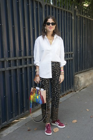 Comment porter: chemise de ville blanche, pantalon carotte imprimé noir, baskets basses en daim bordeaux, sac fourre-tout en cuir multicolore