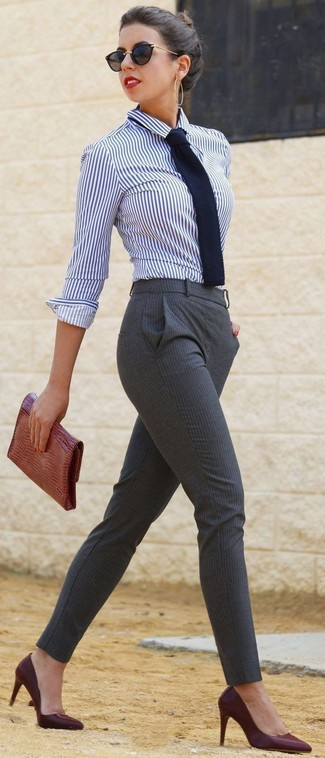 Comment porter: chemise de ville à rayures verticales blanc et bleu marine, pantalon slim à rayures verticales gris, escarpins en cuir bordeaux, pochette en cuir imprimée serpent tabac