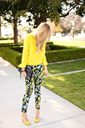 Comment porter: chemise de ville en chiffon jaune, pantalon slim à fleurs noir, sandales à talons en cuir jaunes, pochette en cuir noire