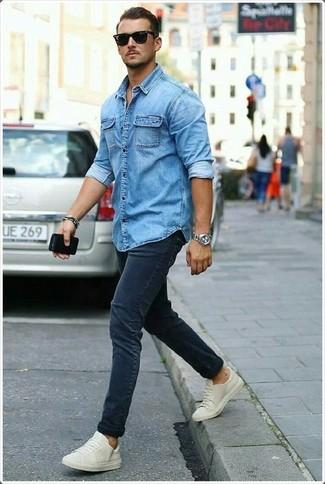 Comment porter: chemise en jean bleue, jean skinny bleu marine, baskets basses beiges, lunettes de soleil noires