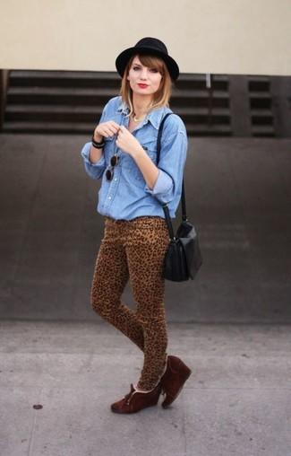 Comment porter: chemise en jean bleue, jean skinny imprimé léopard marron clair, bottines compensées en daim marron foncé, sac bandoulière en cuir noir