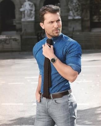 Comment porter: chemise en jean bleue, jean skinny gris, cravate á pois marron foncé, ceinture en cuir marron foncé