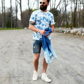 Comment porter: chemise en jean bleue, t-shirt à col rond imprimé tie-dye bleu, short en denim bleu marine, baskets montantes en toile blanches