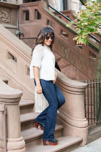 Comment porter: chemisier à manches courtes en dentelle blanc, jean flare bleu marine, mules en cuir noires, sac bandoulière en cuir à franges blanc