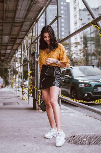Comment porter: chemisier à manches courtes á pois moutarde, minijupe en cuir noire, chaussures de sport blanches, cartable en cuir noir