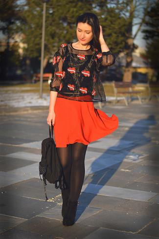 Comment porter: chemisier à manches courtes imprimé noir, jupe patineuse rouge, bottines en daim noires, sac à dos en toile noir