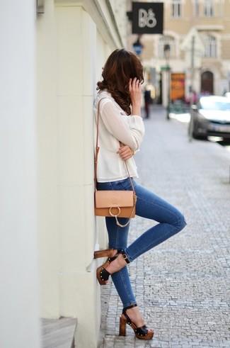 Comment porter: chemisier à manches longues en soie blanc, jean skinny déchiré bleu, sandales à talons en cuir noires, sac bandoulière en cuir marron clair