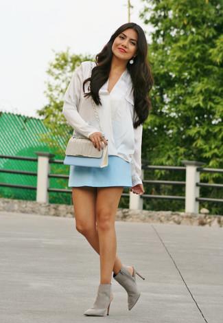 Comment porter une minijupe bleu clair: Marie un chemisier à manches longues en soie blanc avec une minijupe bleu clair pour une tenue idéale le week-end. Une paire de des bottines en daim découpées grises est une option parfait pour complèter cette tenue.
