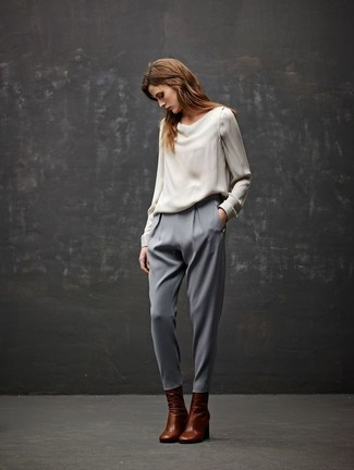 Tenue: Chemisier à manches longues en soie blanc, Pantalon carotte gris, Bottines en cuir marron