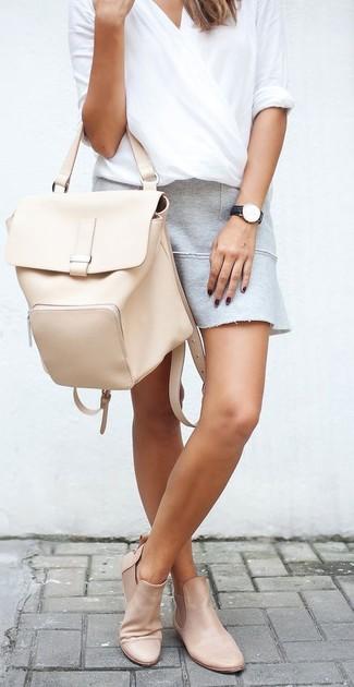 Comment porter: chemisier à manches longues blanc, minijupe grise, bottines chelsea en cuir beiges, sac à dos en cuir beige