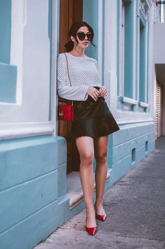 Comment porter: chemisier à manches longues á pois blanc et noir, minijupe en cuir plissée noire, escarpins en cuir rouges, sac bandoulière en cuir rouge