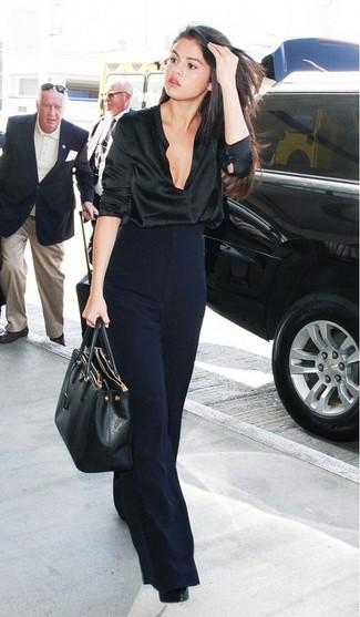 Comment porter: chemisier à manches longues en satin noir, pantalon large bleu marine, escarpins en cuir noirs, sac fourre-tout en cuir noir
