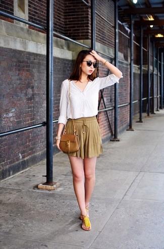 Comment porter: chemisier à manches longues à rayures verticales blanc, short plissé marron clair, tongs en cuir à franges jaunes, sac bandoulière en cuir marron