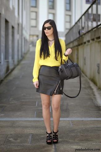 Comment porter: chemisier boutonné en soie jaune, minijupe en cuir noire, sandales à talons en cuir noires, sac à main en cuir orné noir