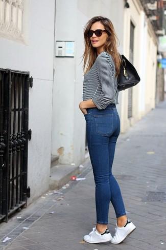 Comment porter: chemisier boutonné à rayures verticales blanc et noir, jean skinny bleu, baskets basses en toile blanches, cartable en cuir noir